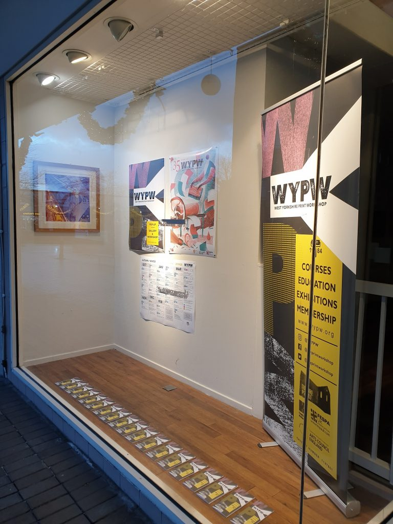unit 2 The Piazza, Huddersfield, shop front display with framed print, posters and banner.