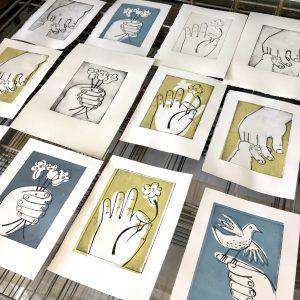 Colour drypoint prints drying on a rack.